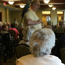 Bird Show-Eagan Pointe Senior Living-Brad showing off one of their parrots