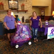 national-night-out-alzheimers-association-fundraiser-eagan-pointe-senior-living-women showing off the raffle prizes