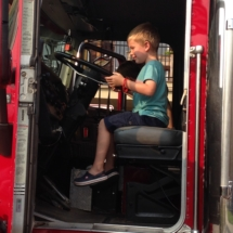 national-night-out-alzheimers-association-fundraiser-eagan-pointe-senior-living-little boy driving a firetruck