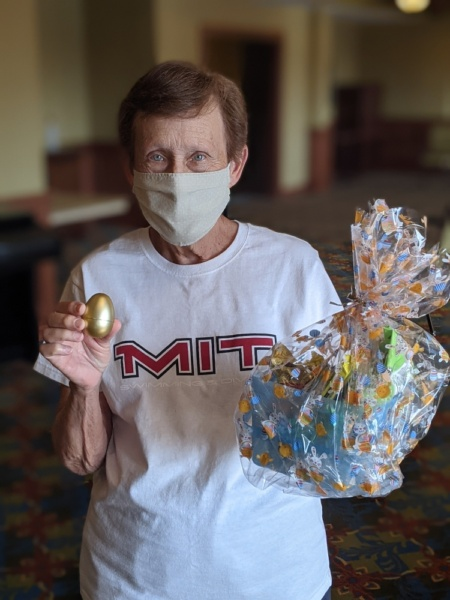 Joan D. holds up the prized golden egg and her prize for finding it - an Easter basket full of goodies.